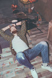 Bearded man lying on floor in messy room after party Royalty Free Stock Images