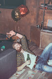 Bearded man lying on floor in messy room after party Stock Photo