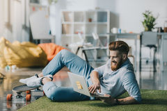 Bearded man lying on floor and using laptop in creative office Royalty Free Stock Photos