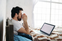Bearded man lying in morning bed with laptop Stock Photos