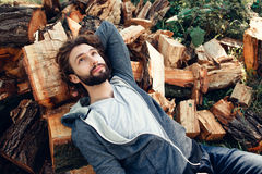 Bearded man lying on pile of wood and dreaming Stock Photography
