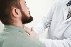 Bearded man on lymph nodes examination in doctor. Cropped close up of bearded men face on medical examination. Doctor in white, medical uniform touching neck stock photo