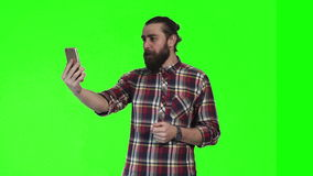 Bearded man make video call. Bearded caucasian young man make video call using smartphone on green screen background stock video