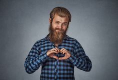 Bearded man making heart gesture with fingers stock image
