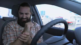 Bearded man massaging wrist while driving car, injured hand, joint inflammation