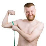 Bearded man measures his little biceps Stock Image