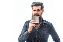 Bearded man with metallic flask. Handsome bearded fashion man with stylish hair mustache and long beard sniffing and hoilding metallic flask isolated on white Royalty Free Stock Photo