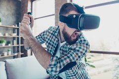 Bearded man in motion, getting experience wearing vr goggles, pl. Aying video game, holding console in hand like trying to fight with someone Stock Images