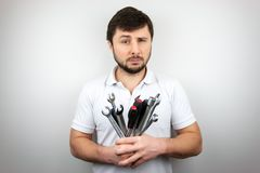 A bearded man with narrowed one eye with a bouquet of wrenches and screwdrivers. A bearded man with narrowed one eye in a white t-shirt with a bouquet of stock photos