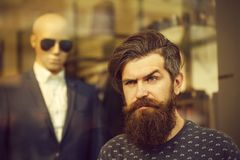 Bearded man near showcase with dummy. Handsome bearded young man hipster with long beard and mustache has stylish hair on serious hairy face standing near shop Royalty Free Stock Image
