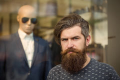 Bearded man near showcase with dummy. Handsome bearded young man hipster with long beard and mustache has stylish hair on serious hairy face standing near shop Stock Images