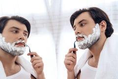 Bearded man neatly shaves beard in shaving foam. royalty free stock image