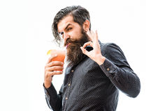 Bearded man with nonalcoholic cocktail. Handsome bearded man with stylish hai mustache and long beard on serious face holding glass of nonalcoholic cocktail and Stock Images