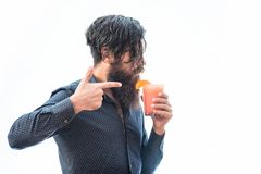 Bearded man with nonalcoholic cocktail. Handsome bearded man with stylish hair that fell on face mustache and long beard drinking and holding glass of Stock Photos