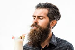 Bearded man with nonalcoholic cocktail. Handsome bearded man with stylish hair mustache and long beard holding and looking on glass of nonalcoholic cocktail Stock Photos