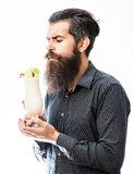 Bearded man with nonalcoholic cocktail. Handsome bearded man with stylish hair mustache and long beard holding and looking on glass of nonalcoholic cocktail  on Royalty Free Stock Image