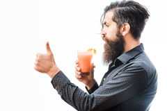 Bearded man with nonalcoholic cocktail. Handsome bearded man with stylish hair mustache and long beard on serious face drinking and holding glass of nonalcoholic Royalty Free Stock Images