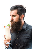 Bearded man with nonalcoholic cocktail. Handsome bearded man with stylish hair mustache and long beard on serious face holding glass and drinking nonalcoholic Royalty Free Stock Images