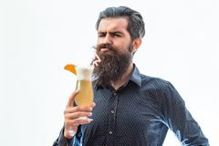 Bearded man with nonalcoholic cocktail. Handsome bearded man with stylish hair mustache and long beard on sullen face holding glass and drinking nonalcoholic Royalty Free Stock Image
