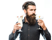 Bearded man with nonalcoholic cocktails. Handsome bearded man with stylish hair mustache and long beard on serious face drinking and holding glass of Royalty Free Stock Images