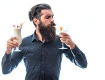 Bearded man with nonalcoholic cocktails. Handsome bearded man with stylish hair mustache and long beard on serious face drinking and holding glass of Royalty Free Stock Photography