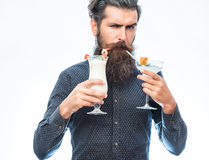 Bearded man with nonalcoholic cocktails. Handsome bearded man with stylish hair mustache and long beard on serious face holding glass of nonalcoholic cocktails Stock Photos