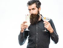 Bearded man with nonalcoholic cocktails. Handsome bearded man with stylish hair mustache and long beard on serious face holding glass of nonalcoholic cocktails Royalty Free Stock Image