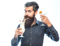 Bearded man with nonalcoholic cocktails. Handsome bearded man with stylish hair mustache and long beard on serious face holding glass of nonalcoholic cocktails Royalty Free Stock Images