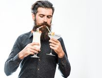 Bearded man with nonalcoholic cocktails. Handsome bearded man with stylish hair mustache and long beard on serious face looking and holding glass of nonalcoholic Royalty Free Stock Photos