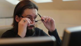 Bearded man in office take off his glasses stock video footage