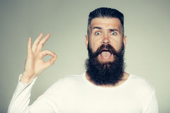Bearded man with okey gesture. Handsome young man with long beard and moustache on surprised face with okey gesture of finger on grey background in studio Stock Image