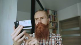 Bearded man online shopping and banking with credit card using smartphone at home. Using app stock video footage