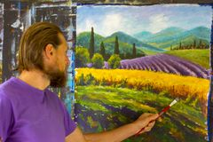 Art creative process. Artist create painting Italian summer countryside. Tuscany. Field of red poppies, a field of yellow rye. Rur. Bearded man painter artist royalty free stock photos