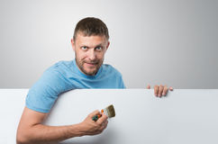 Bearded man paints the white banner Royalty Free Stock Photo