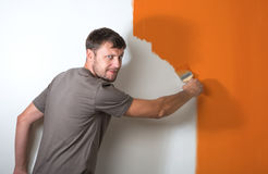 Bearded man paints the white wall Royalty Free Stock Photo