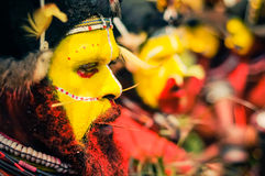 Bearded man in Papua New Guinea. Hagen show, Papua New Guinea - circa August 2015: Native bearded man with yellow colour on face and red on body poses with Stock Image