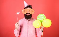 Bearded man with party accessories, surprise concept. Man with paper lips, enormous crazy glasses and balloons isolated. On red background. Hipster with long Royalty Free Stock Image