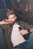 Bearded man with party blower holding beer bottle and looking at camera Royalty Free Stock Photography