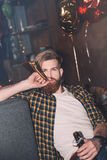 Bearded man with party blower holding beer bottle and looking at camera Royalty Free Stock Images