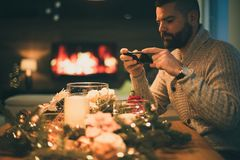Bearded man photographing decorated christmas table Stock Photos