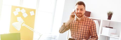 A man stands in the office near a computer desk, puts his hand on the back of the chair and speaks on the phone. A bearded man in a plaid shirt and dark royalty free stock photography
