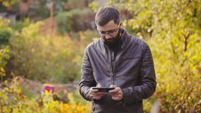 Bearded man play mobile game in the sunny autumn park. Win the game. Holding their smartphone in their hands stock video