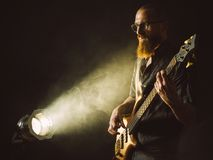 Bearded man playing bass guitar with spotlight Royalty Free Stock Photo