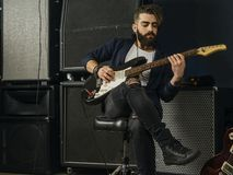 Bearded man playing an electric guitar in a studio stock photography