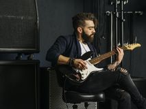 Bearded man playing guitar in a music studio stock photography