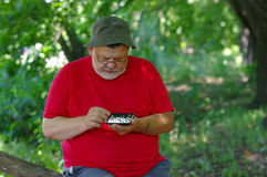 Bearded man playing mini-chess with himself in a park Stock Photo