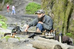 Bearded man prepares coffee in the mountains of the Carpathians, Ukraine Royalty Free Stock Images