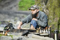 Bearded man prepares coffee in the mountains of the Carpathians, Ukraine Royalty Free Stock Photography