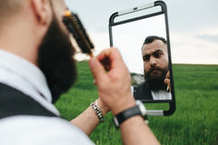 Bearded man preparing to shave in the field Royalty Free Stock Photography