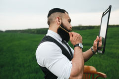 Bearded man preparing to shave in the field Stock Photography